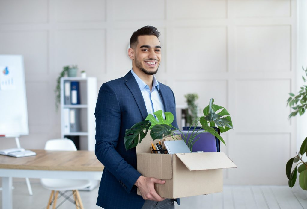First day at office. Portrait of confident Arab businessman with belongings moving to new office