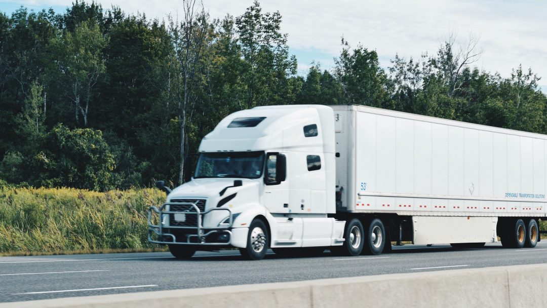 all-white-tractor-trailer-driving-on-a-highway.jpg