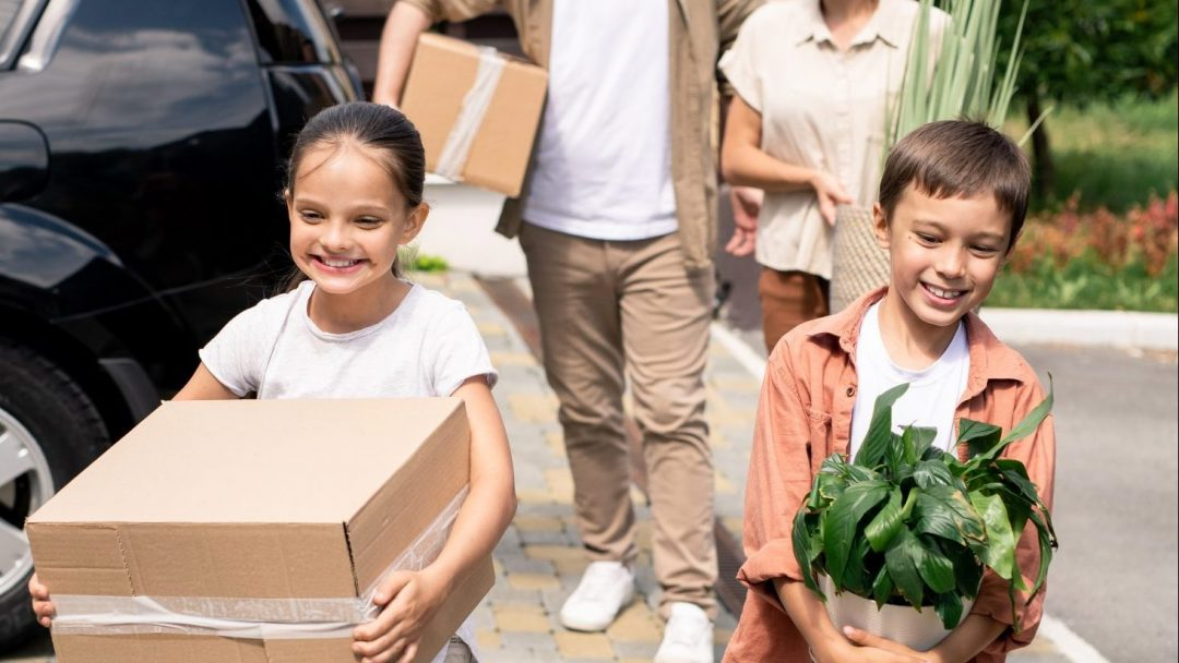 Cheerful cute children carrying moving stuff into new house together with parents